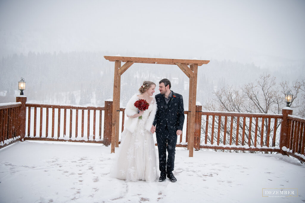Timber Moose Lodge deck covered in snow with the bride and groom