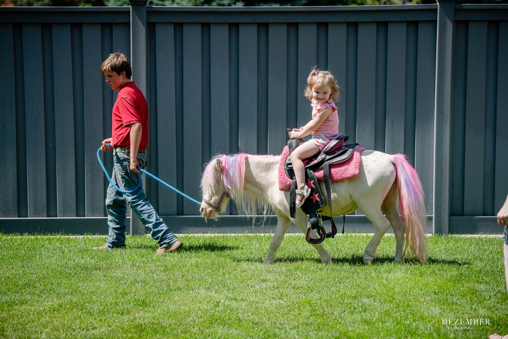 Little girl rides petting zoo pony