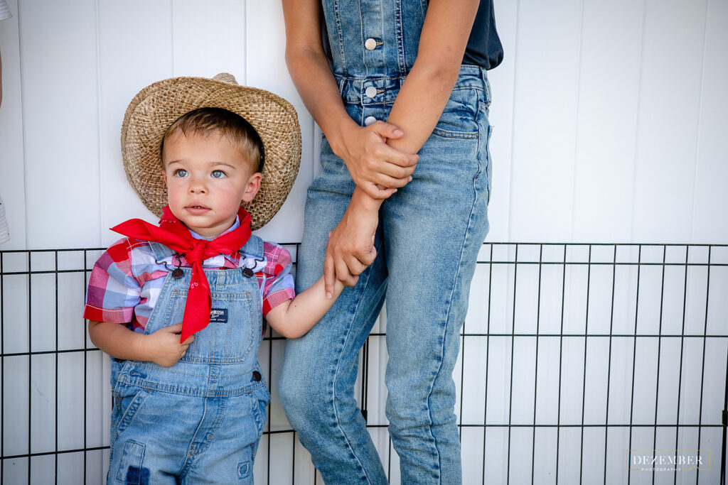 Little boy dressed as farmer holds sister's hand