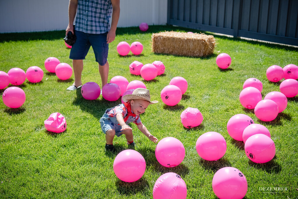 Boy plays with pink piggy inflatable ball