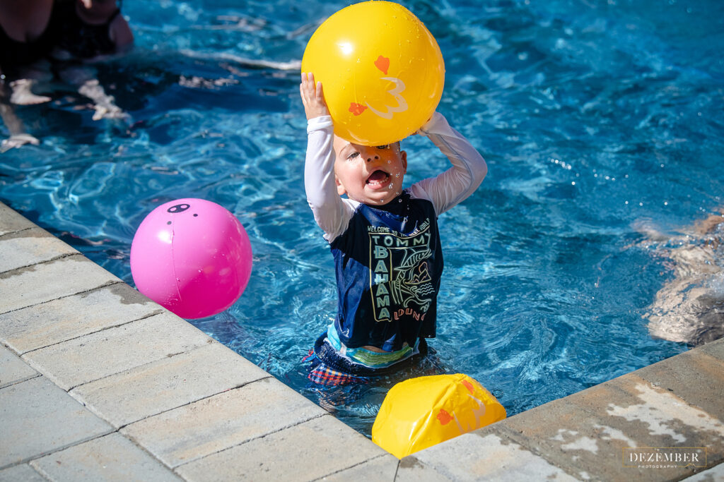 Boy throw yellow ball in the pool