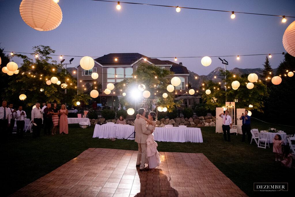 Elegant backyard wedding reception first dance under the string lantern lights