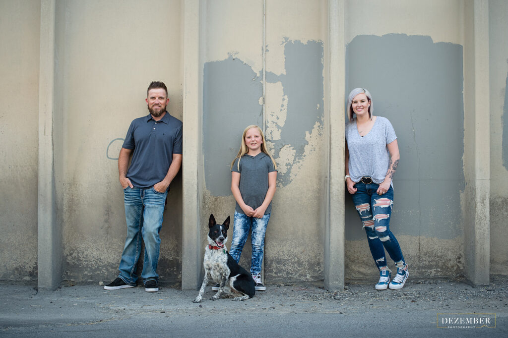 Family posing with their pup on an urban wall