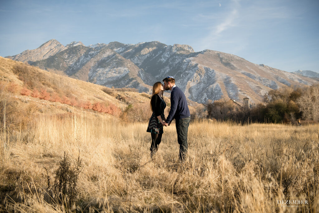 Couple kisses in golden field with mountains in background