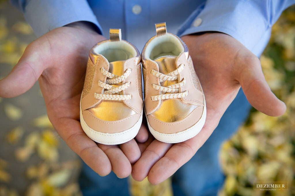 Man holds baby shoes in the palms of his hands
