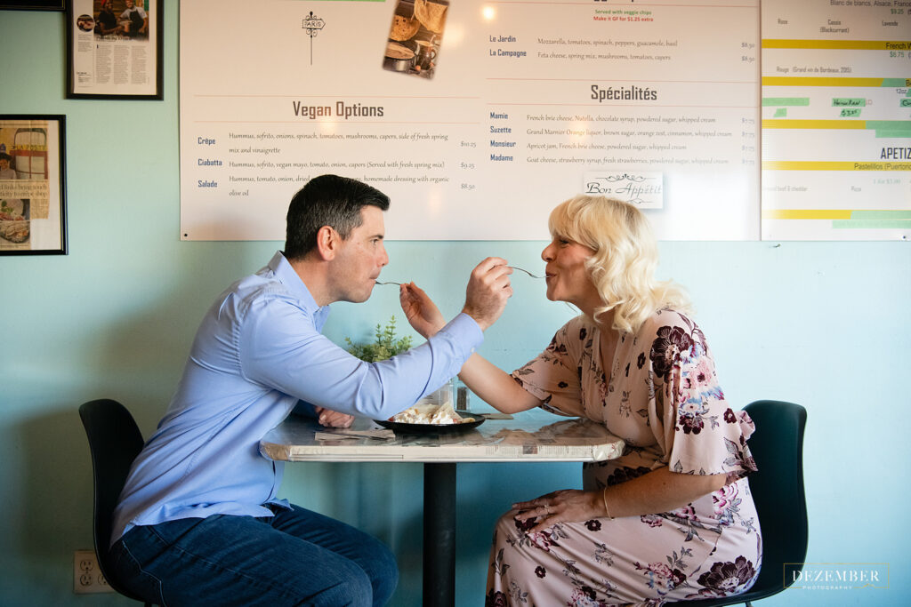 Couple share bites of crepe on their Sugarhouse Maternity session