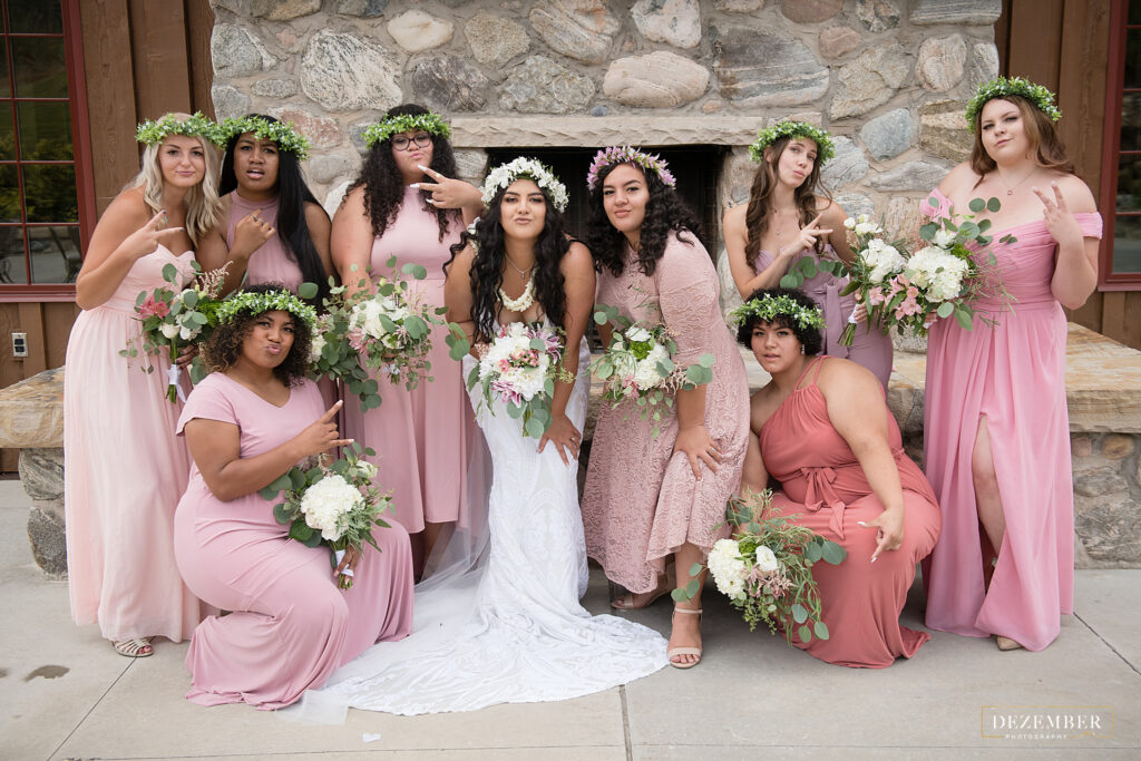 The bride and her bridemaids hold up peace hands for a picture
