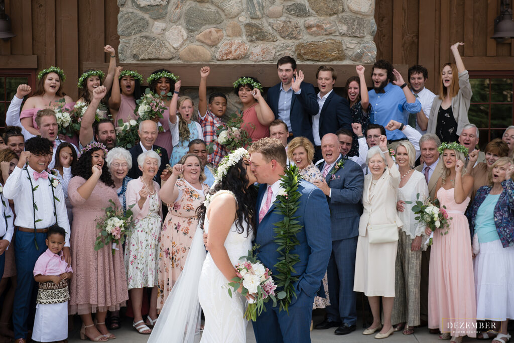 All the family cheers as bride and groom kiss