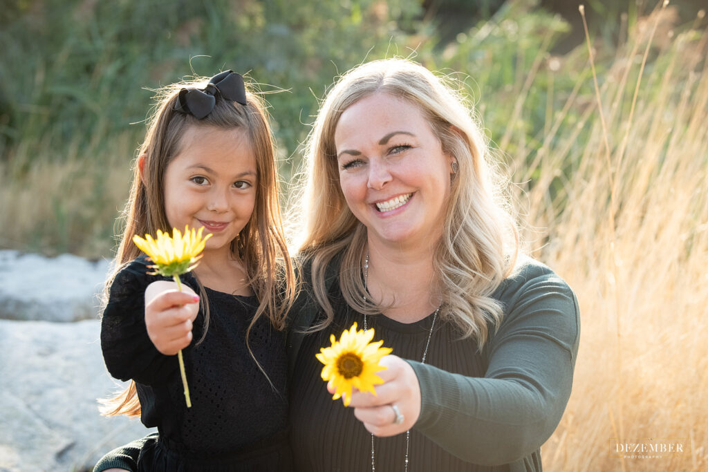 Mom and daughter hold out yellow flowers