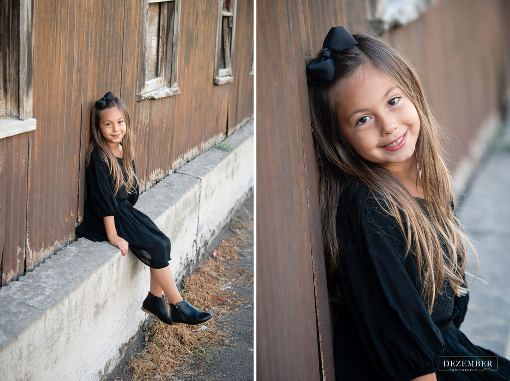 Little girl in black dress smiles for portraits