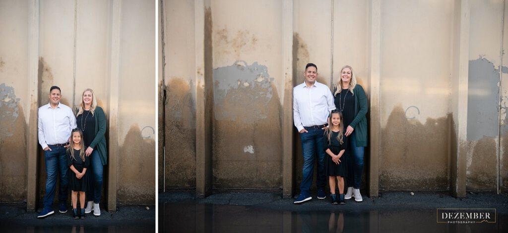 Family poses in front of cement wall