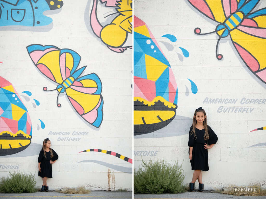 Girl poses in front of butterfly graffiti