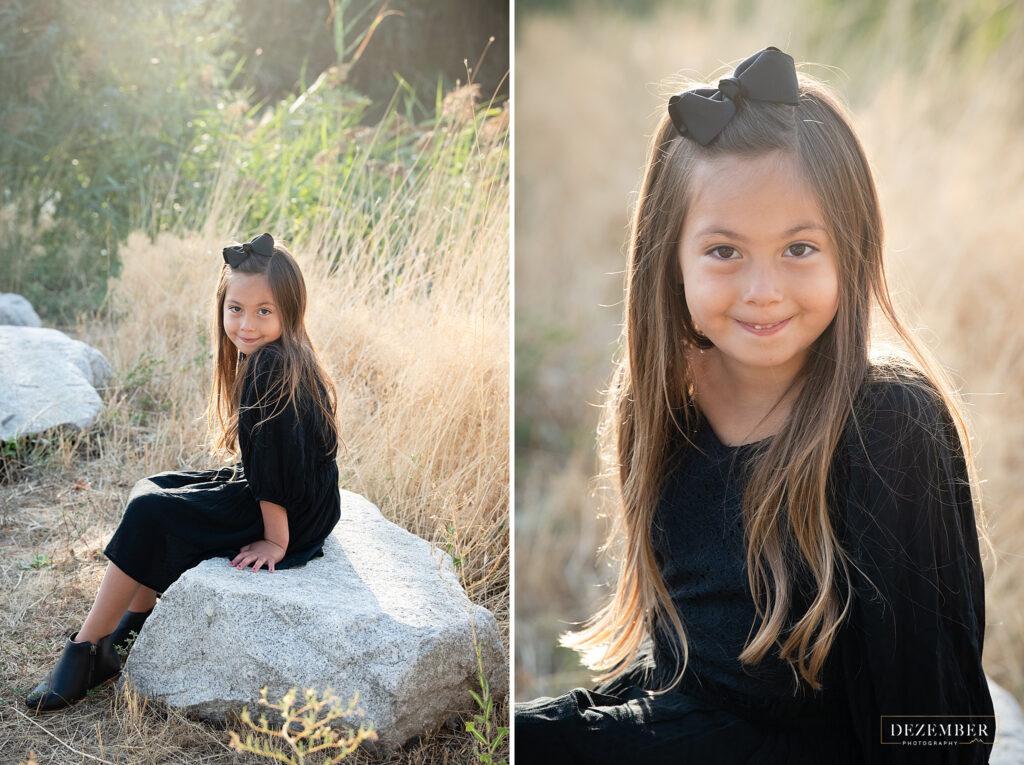 Little girl sits on rock in golden field