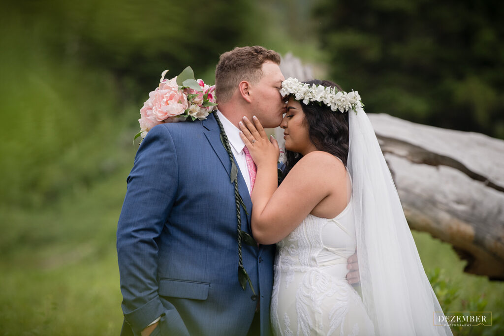 Groom kisses Polynesian bride on the forehead