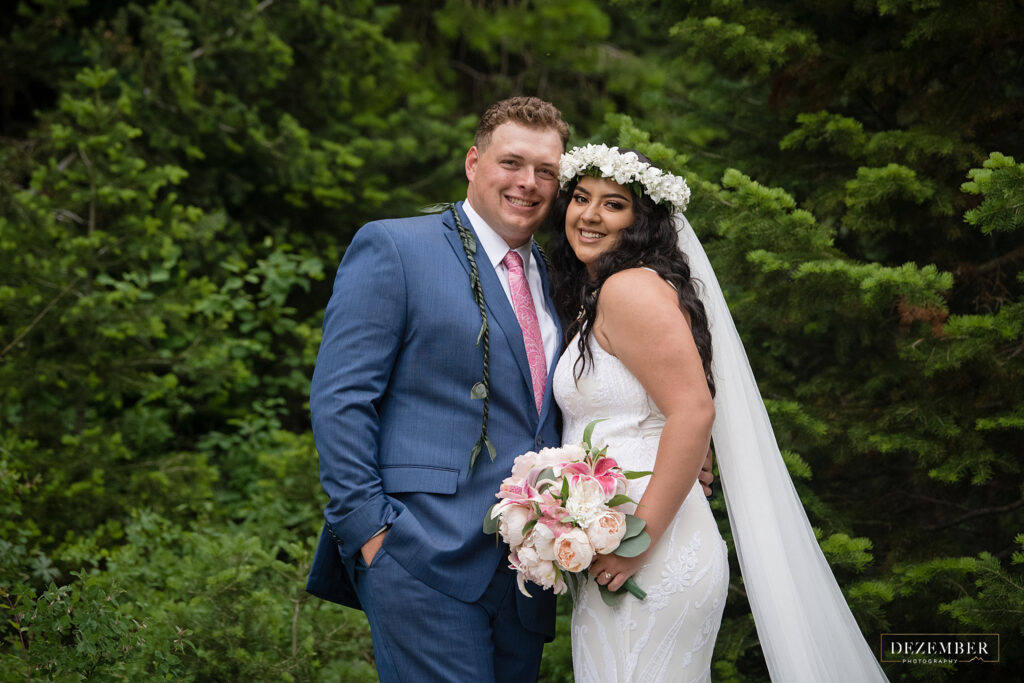 Couple poses in green trees with Polynesian bridal wear
