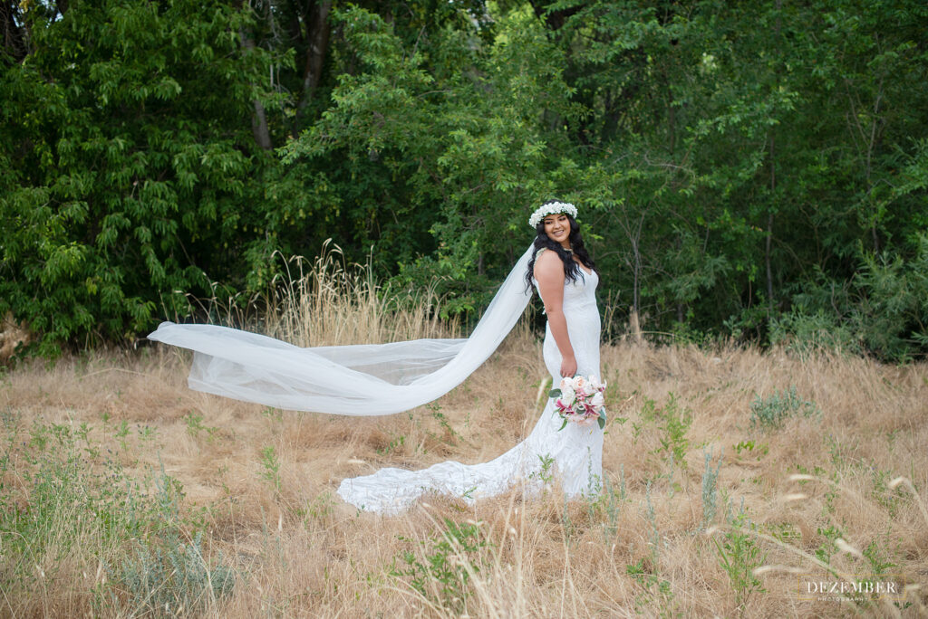 Bride with long train poses in nature