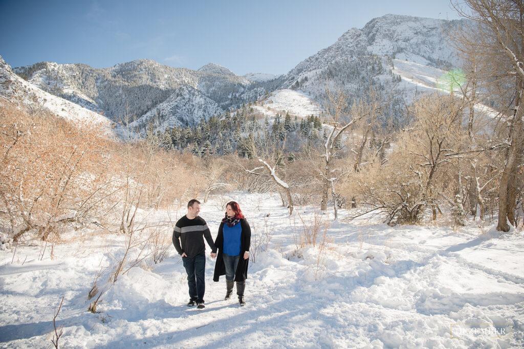 Snow portraits couple walks through trees