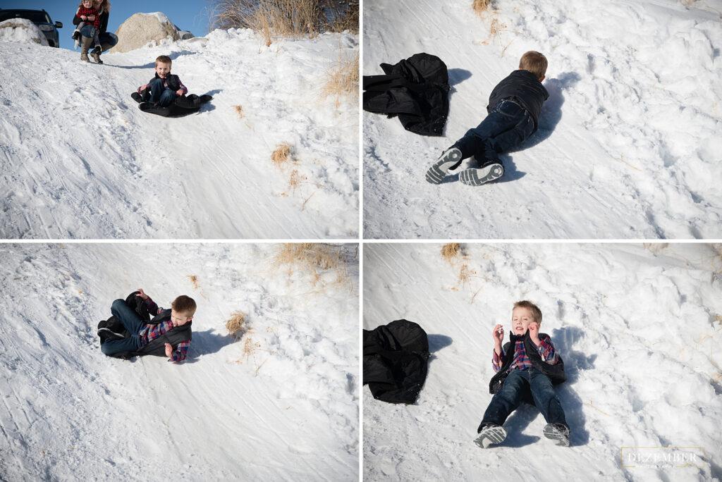 Snowy family portraits boy sledding down hill