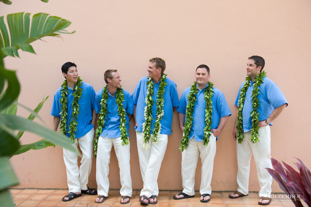 Groomsmen standing in front of a peach wall