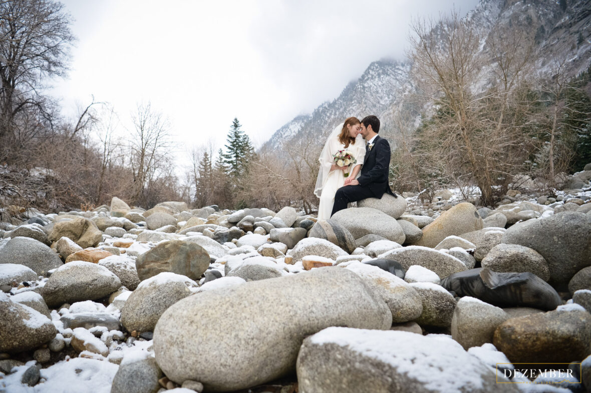 Bride and groom pose in snowy riverbed